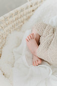 istock Babyfeet in a moses crib beige and whites 1301755352