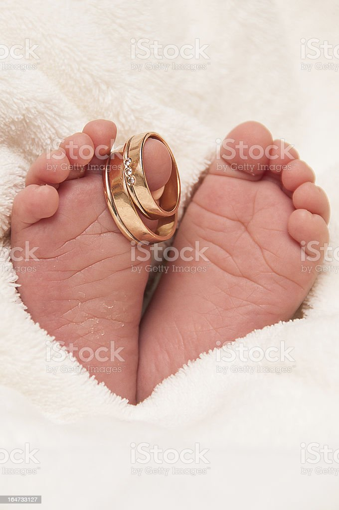 Babyfeet with wedding rings royalty-free stock photo