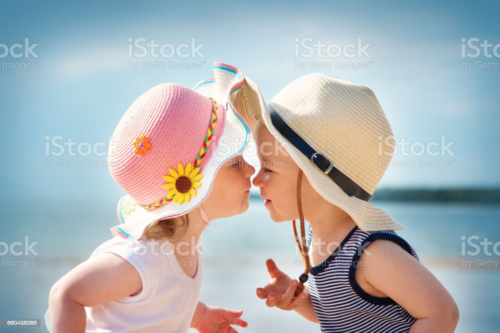 Babygirl and babyboy kissing on the beach stock photo