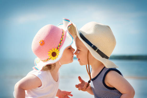babygirl and babyboy kissing on the beach - little girls little boys kissing love stock photos and pictures
