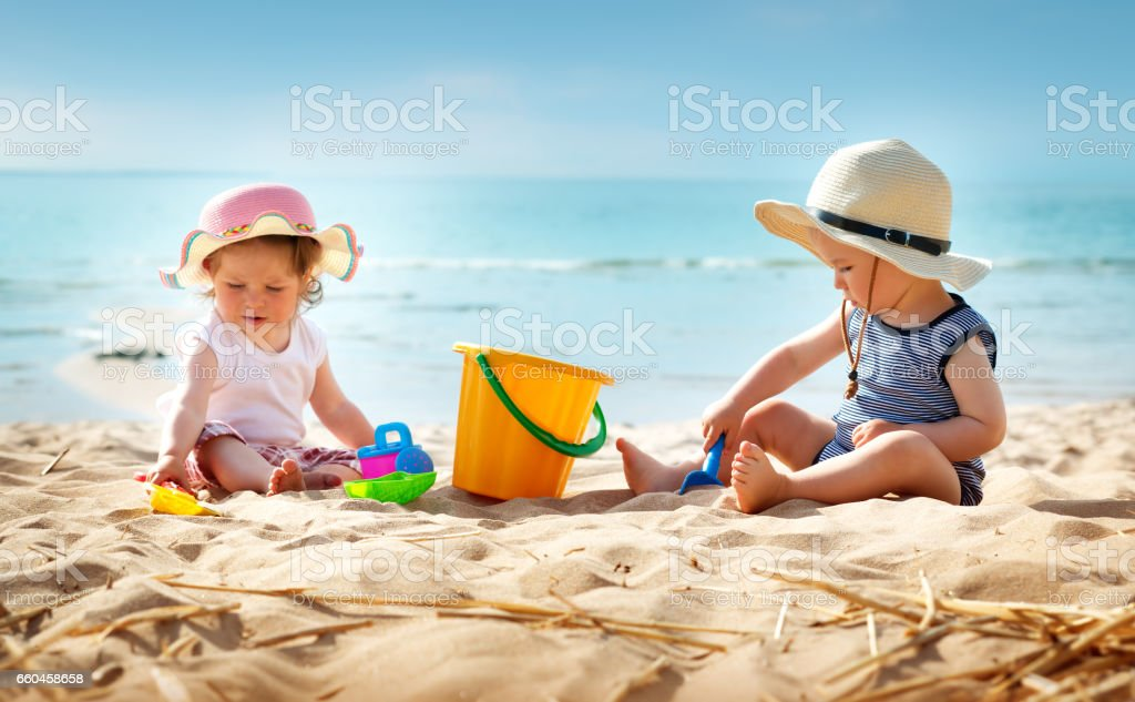 Babygirl and babyboy sitting on the beach
