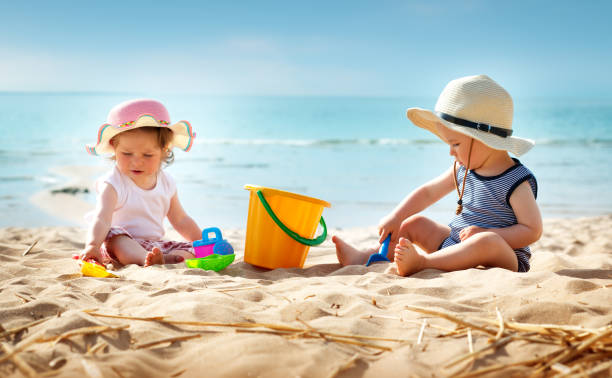 Babygirl and babyboy sitting on the beach - foto stock