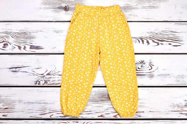 baby-mädchen gelb bedruckt hosen. - bedruckte leggings stock-fotos und bilder