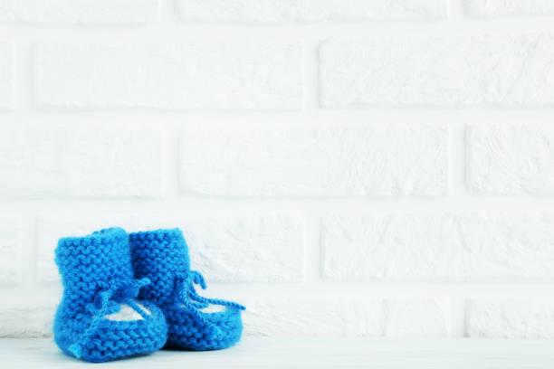 baby schuhe auf dem brick wand hintergrund - babyschuhe nähen stock-fotos und bilder