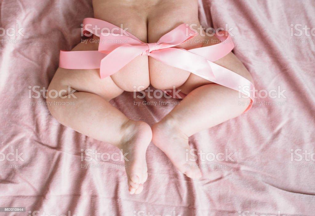 Bebeğin pembe bir yay ile ayak ve kalça stok fotoğrafı