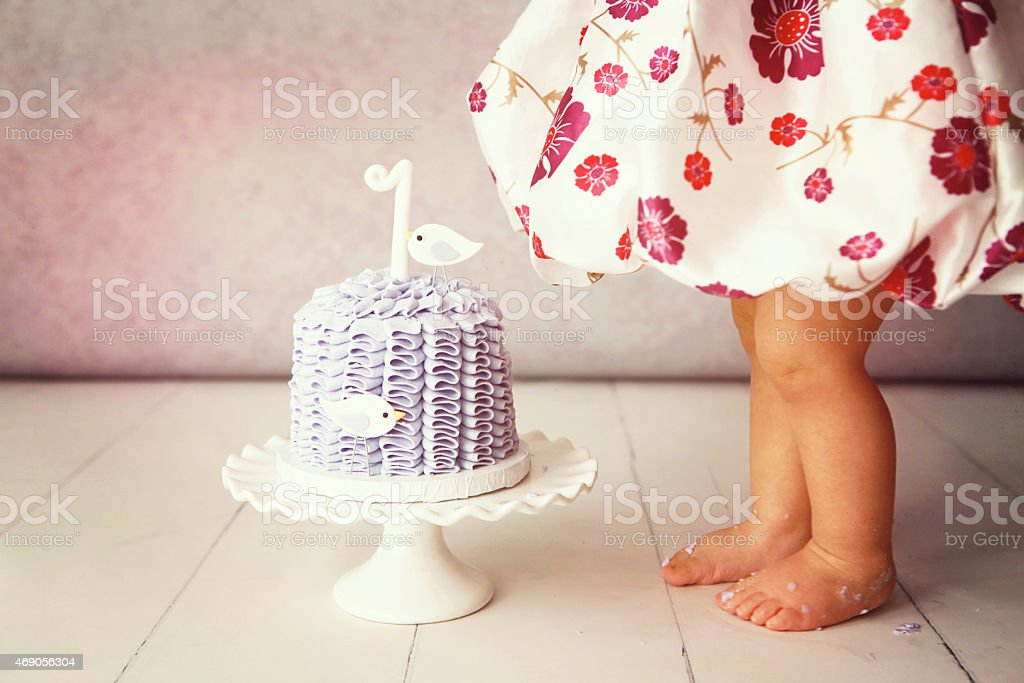 Baby's chubby legs in front of a decorated cake stock photo