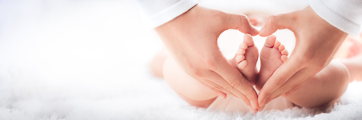 Mother Holding Baby's Feet In Heart Shaped Hands - Infant Care Concept