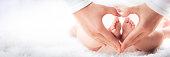 istock Baby's Feet In Heart Shaped Hands 1284638303