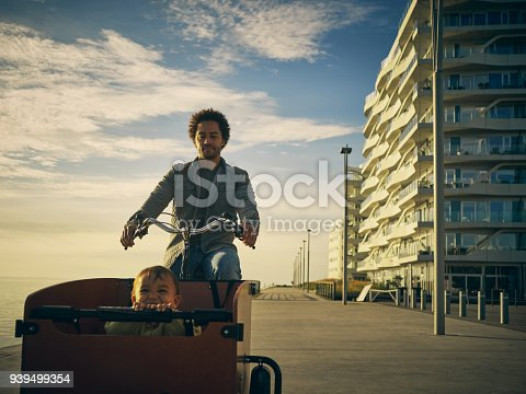 Shot of a young man going for a bicycle ride with his son in a cart along the promenade