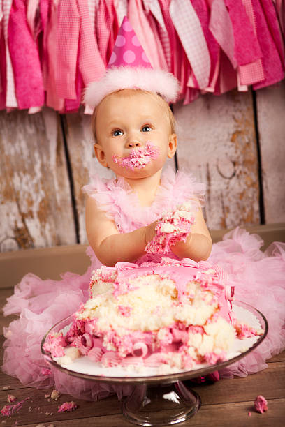 Baby's First Birthday An adorable 1 year old girl eating and smashing a pink birthday cake. first birthday stock pictures, royalty-free photos & images