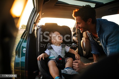 Photo of young father spending time with his son by taking him on a road trip in nature