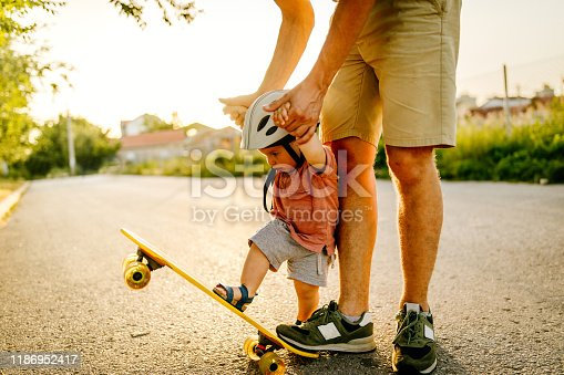 Photo of a baby boy who enjoys his first skateboard ride with a little help from his dad