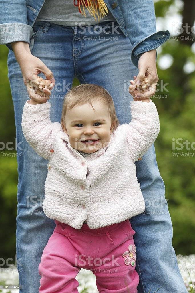 Baby's first steps Mother with baby walking in the park Adult Stock Photo