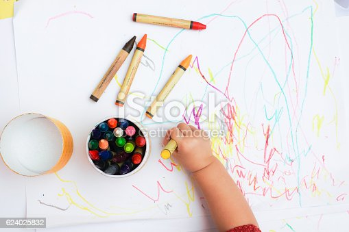 A hand of baby drawing on the white paper with colorful crayons.
