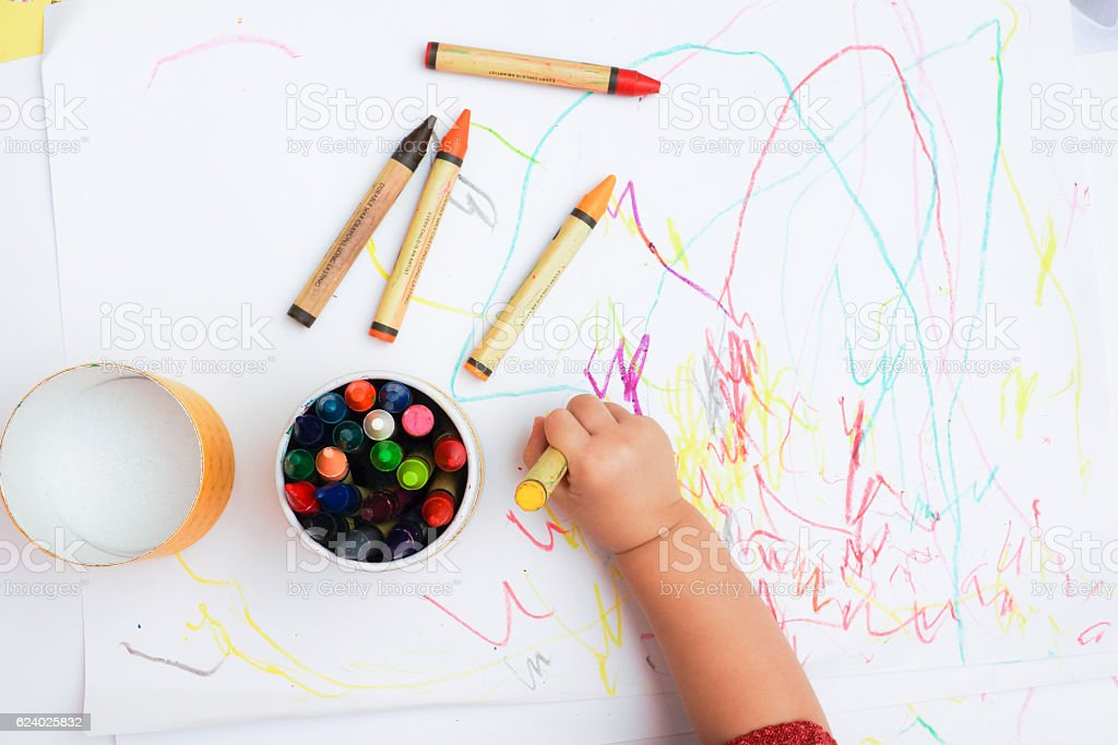 Baby's hand drawing on the white paper with colorful crayons stock photo