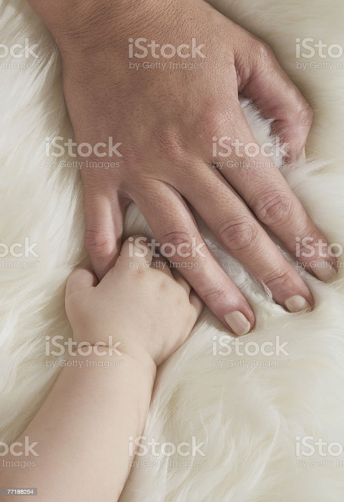 A baby's hand holding a woman's hand royalty-free stock photo