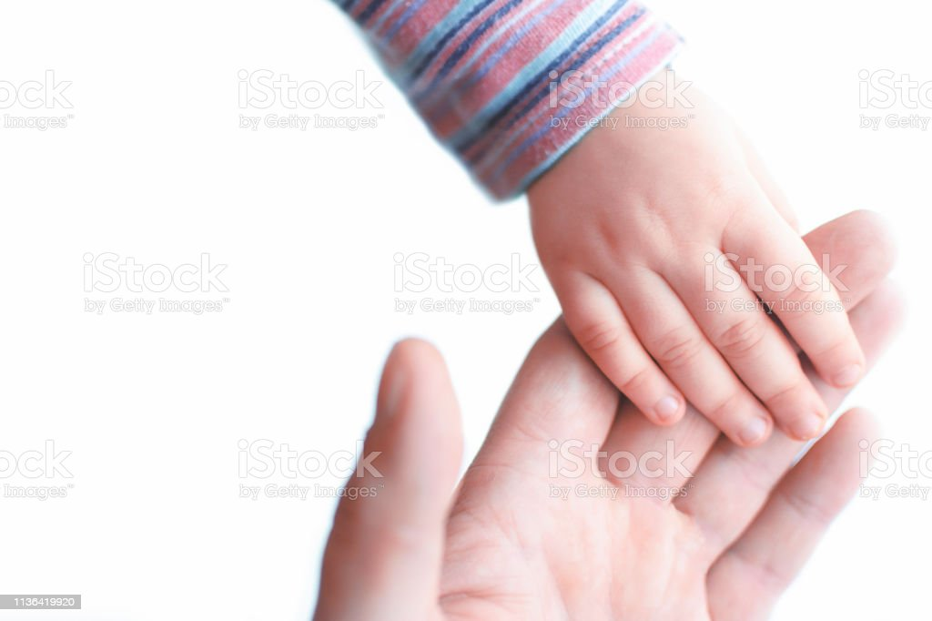 Baby\'s hand lies on the hand of an adult.giving high five
