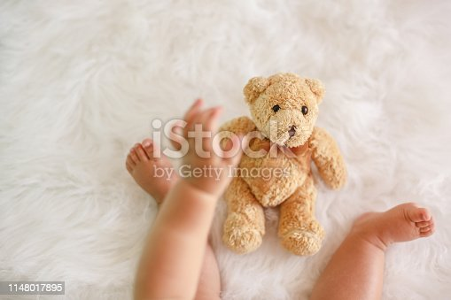 istock Baby's hand reaching for teddy bear toy 1148017895