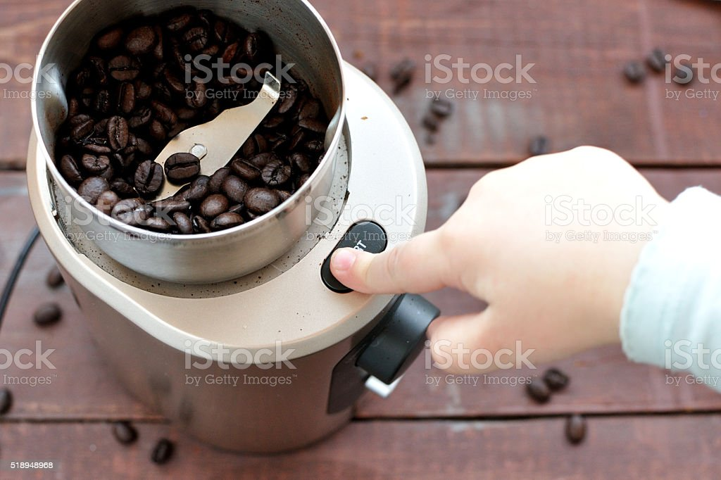 Baby's hand reaching start button of electric coffee grinder stock photo