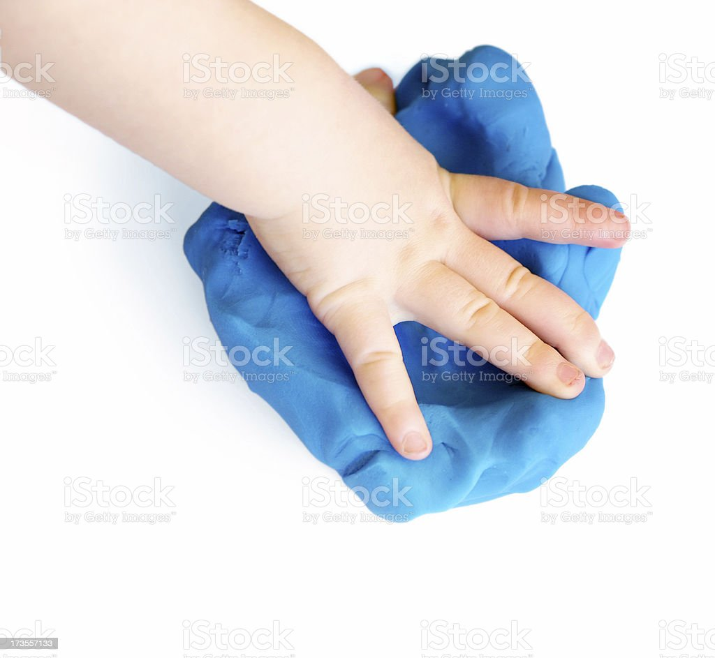 Baby's hand squishing blue play-d'oh stock photo