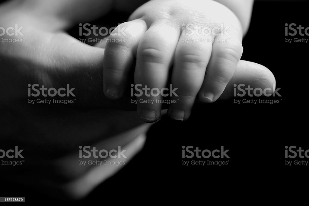 Baby's hand wrapped around adult's forefinger in greyscale stock photo