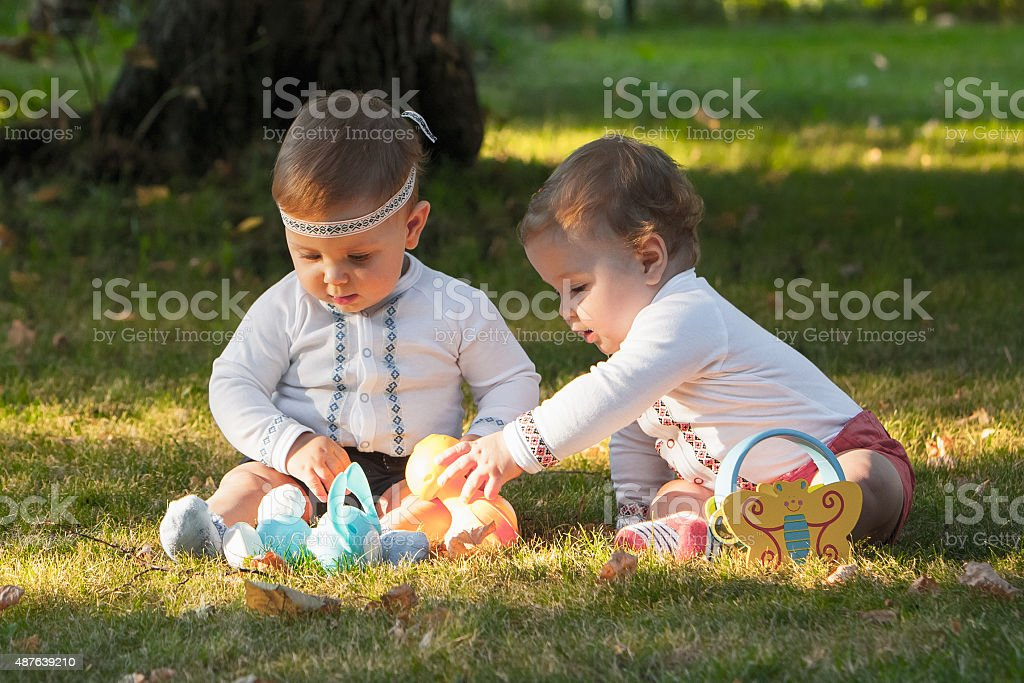 Babys, less than a year old, playing with  toys stock photo
