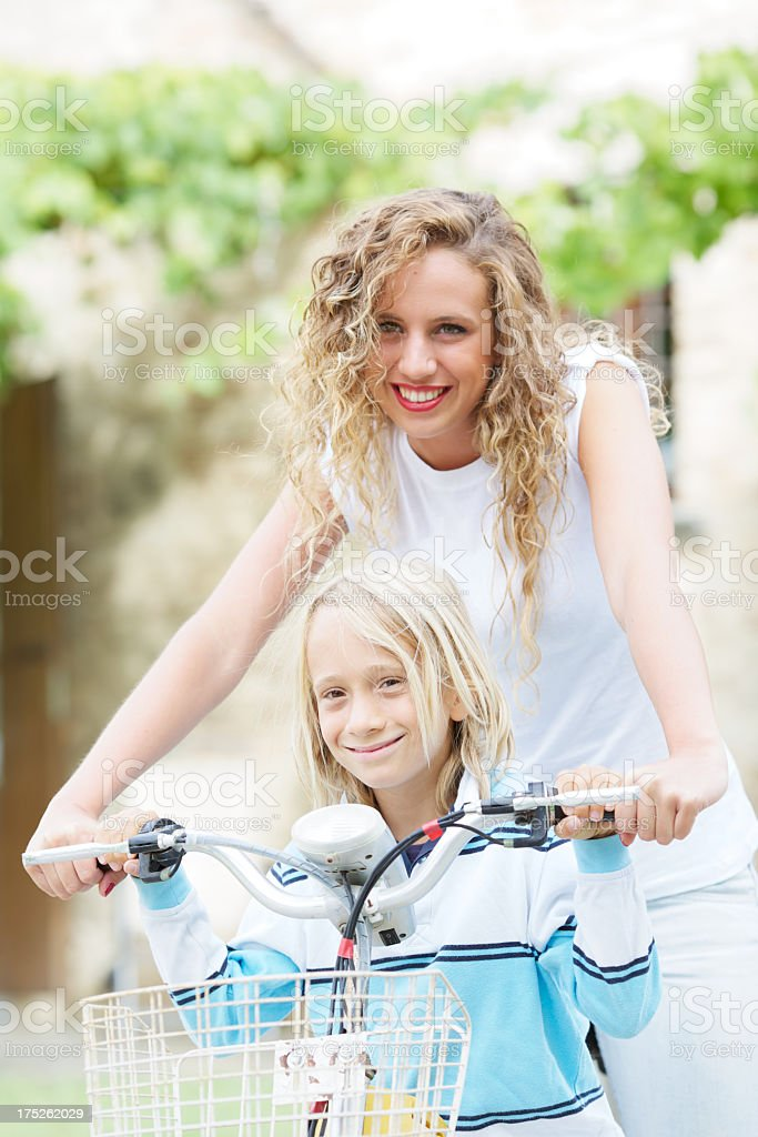 A babysitter helping a little bit on his bike royalty-free stock photo