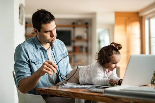 Babysitting and working at home! Stay at home father feeling stressed while baby sitting and trying to work while his small daughter is using his laptop. stay at home father stock pictures, royalty-free photos & images