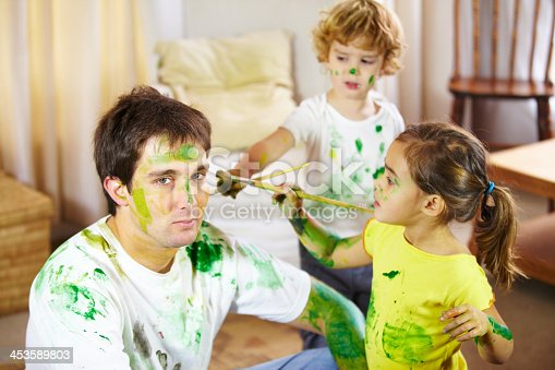 Resigned young father being painted by his two children