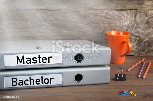 istock Bachelor and Master - two folders on wooden office desk 645948744