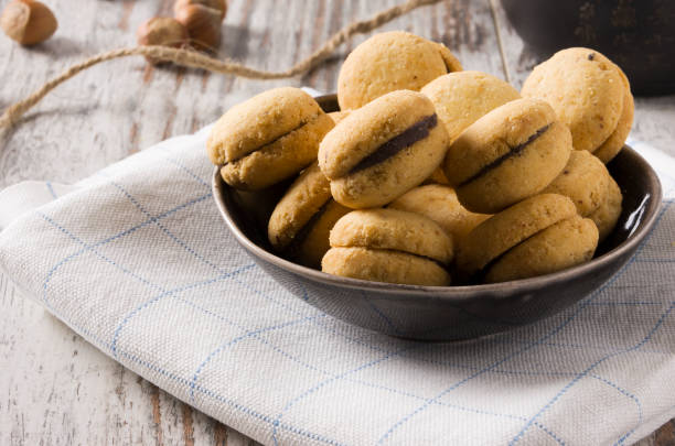 Baci di dama: delicious chocolate cookies with hazelnuts and topping - foto stock