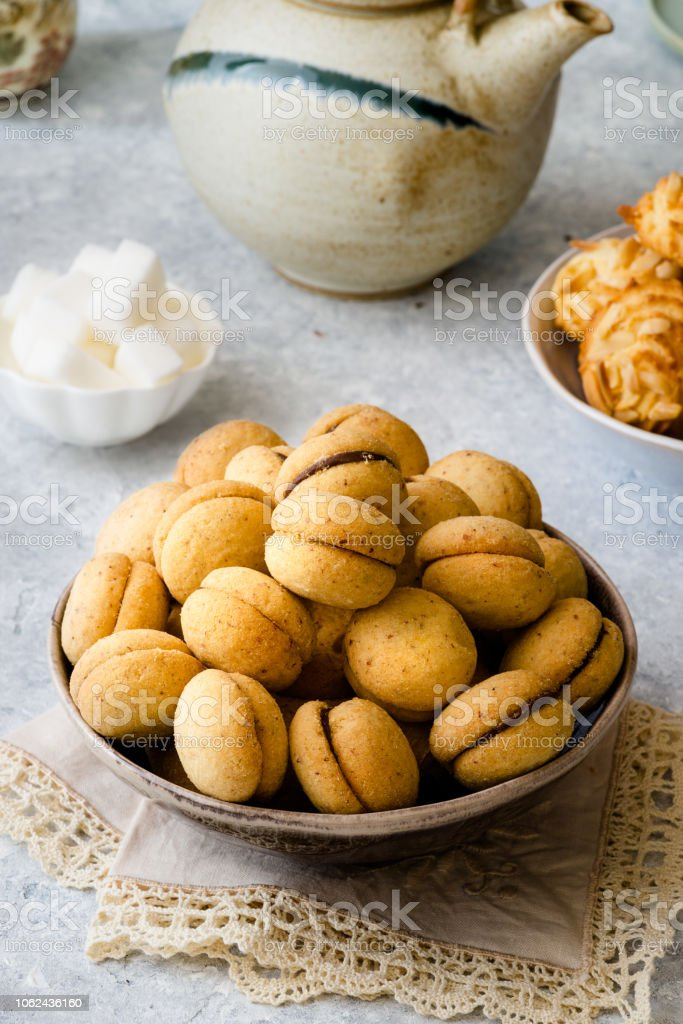 'Baci di dama': italian delicious cookies with chocolate and hazelnuts and topping on delicate background - foto stock