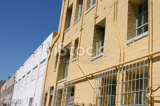 Freshly painted businesses facing the alley with security bars on windows and bright light and diminishing perspective
