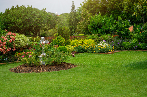 Back and front yard English cottage garden, smooth green grass lawn, colorful flowering plant and orange brick wall, evergreen trees on background, in good care maintenance landscaped in the park