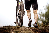 back athlete cyclist with dirty mountain bike climb uphill
