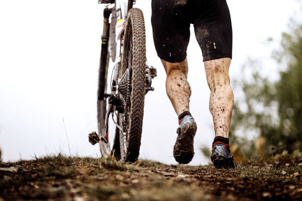 back athlete cyclist with dirty mountain bike climb uphill stock photo