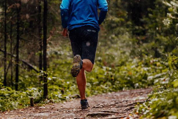 back athlete runner running under drops of rain forest trail stock photo