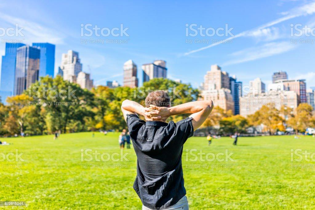 Volta o close de uma jovem feliz com as mãos atrás da cabeça, de pé no Central Park em Nova Iorque durante o dia ensolarado de Outono com edifícios arranha-céus e as pessoas - foto de acervo