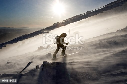 Back country skier walking up under a frozen cable of an old ski lift, in a severe windy weather.