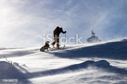 Back country skier hiking with his dog in the winter mountain in cold winter day.
