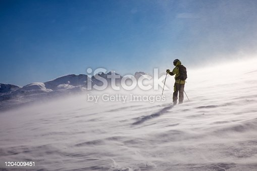 Back country skier moving forward on the top of the slope in harsh weather conditions