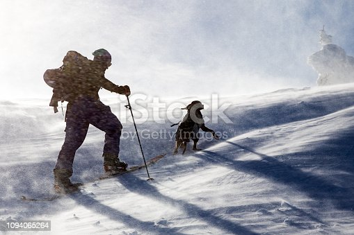 Back country snowboarder hiking with his dog in the winter mountain in cold winter day.