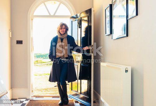 A woman holding her front door open, having returned home from a walk in the British countryside.