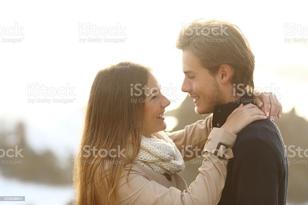 Back light of a couple looking each other stock photo
