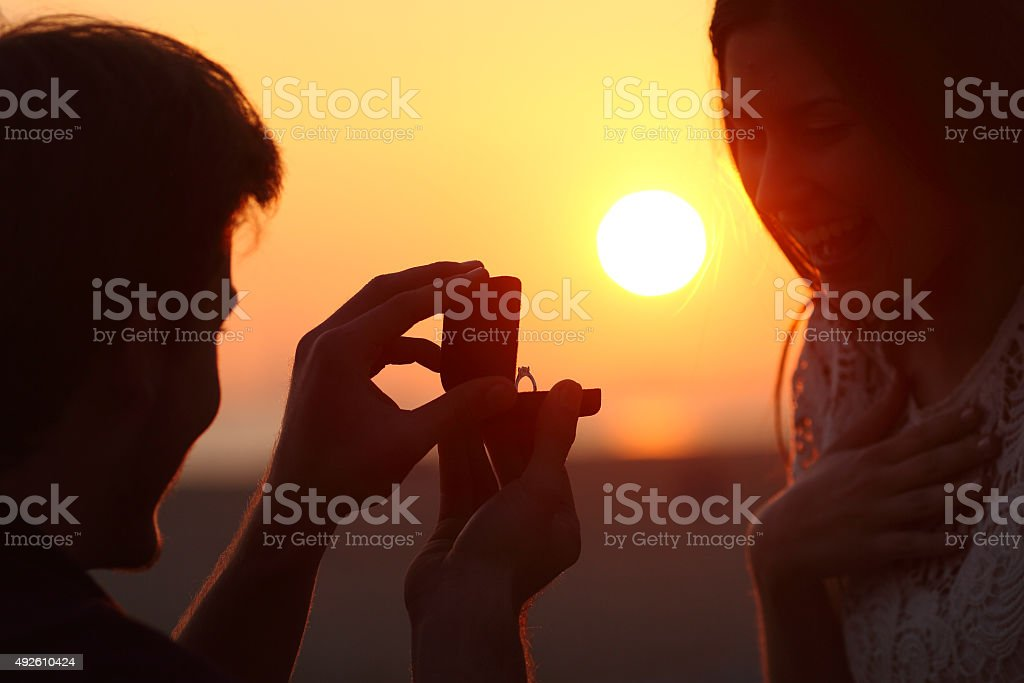 Back light of a proposal of marriage at sunset stock photo