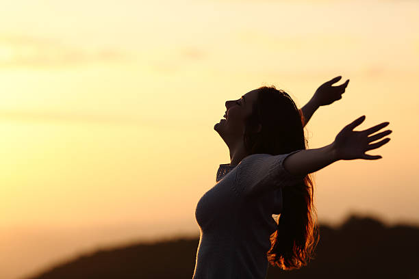 back light of a woman breathing raising arms - arms outstretched stock photos and pictures