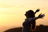 Back light of a woman breathing raising arms