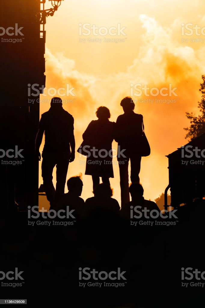 Back lit image of a group of people walking on the street at sunset....