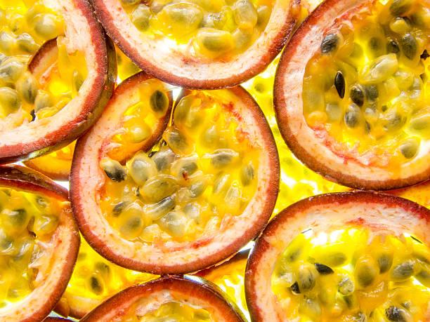 back lit slices of ripe maracuja passion fruit - fruit de la passion photos et images de collection