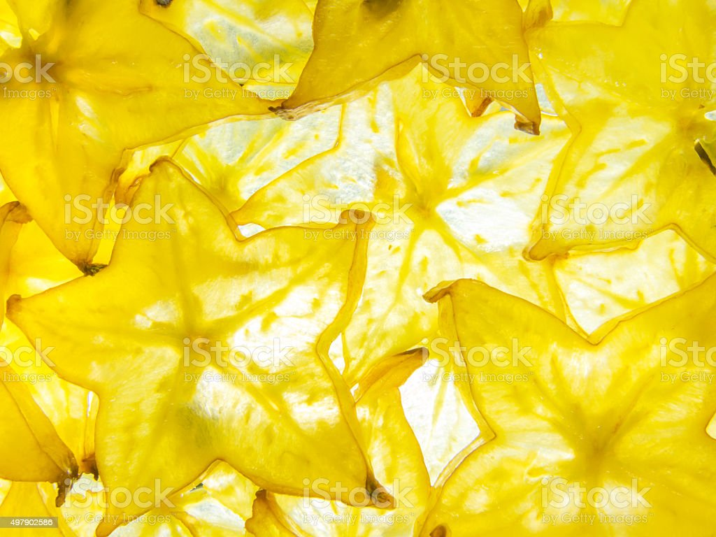 back lit yellow ripe slices of star fruit carambola stock photo
